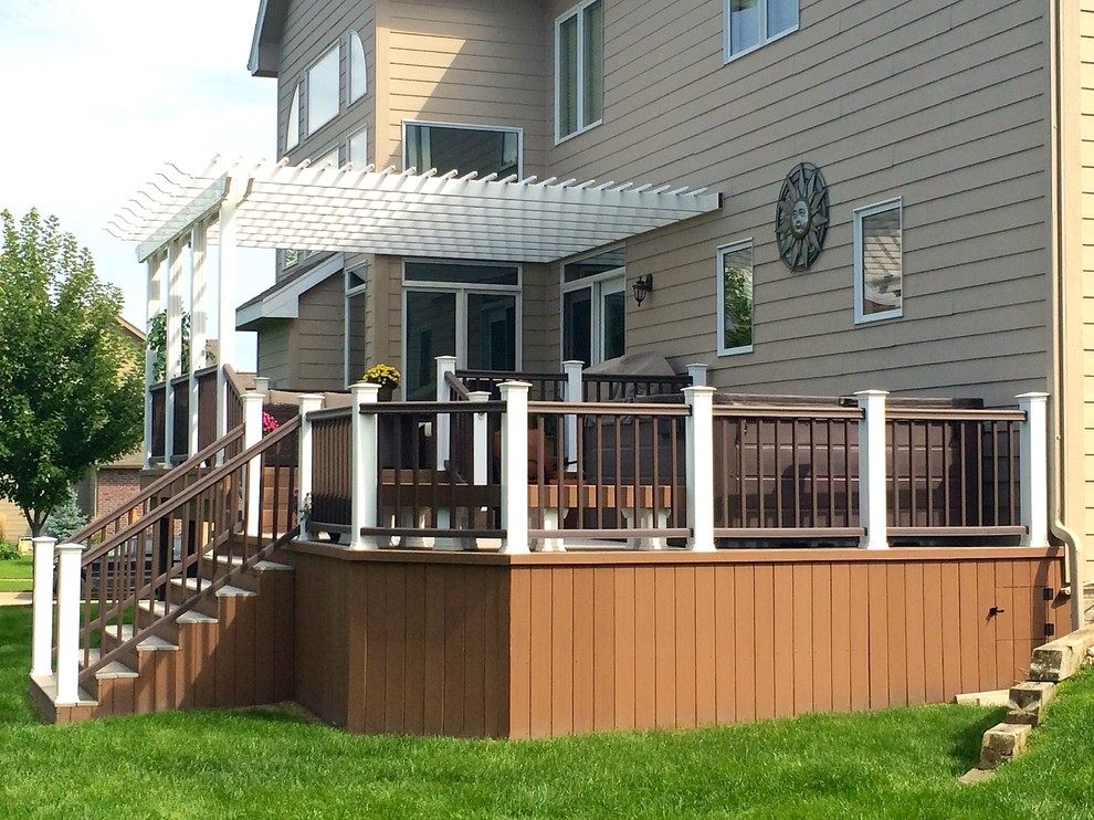Example of a mid-sized classic backyard deck design in Other with a pergola