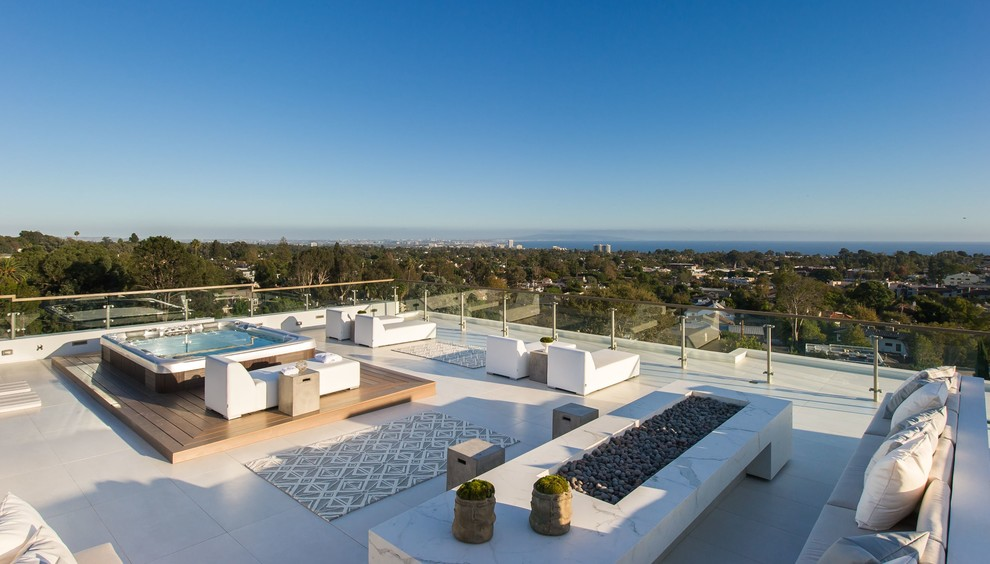 Example of a huge trendy rooftop deck design in Los Angeles with a fire pit and no cover