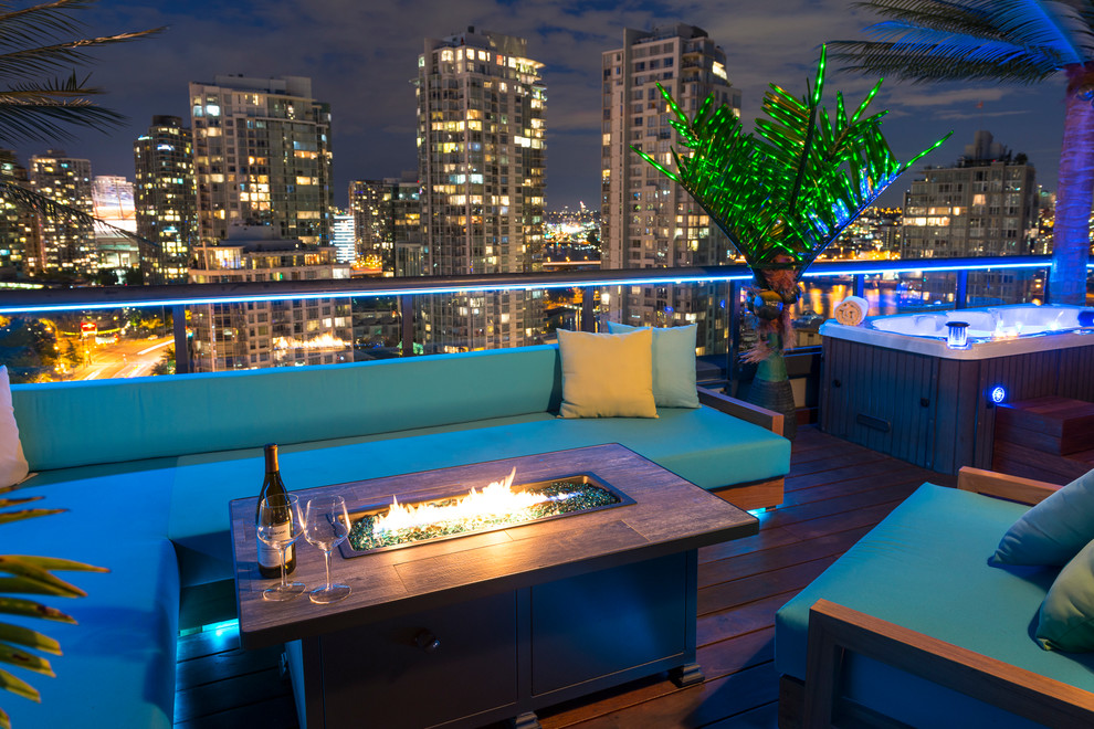 Inspiration for a small tropical rooftop deck remodel in Vancouver with a fire pit