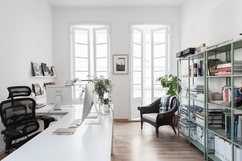 Example of a mid-sized danish freestanding desk light wood floor study room design in Other with white walls