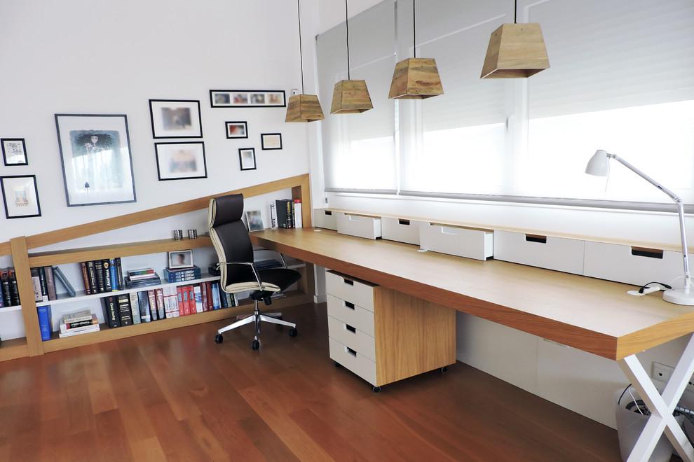Ejemplo de despacho nórdico, de tamaño medio, con paredes blancas, suelo de madera en tonos medios y escritorio empotrado