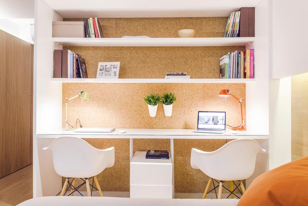 Ejemplo de despacho nórdico, pequeño, sin chimenea, con paredes marrones, escritorio empotrado y suelo de madera clara