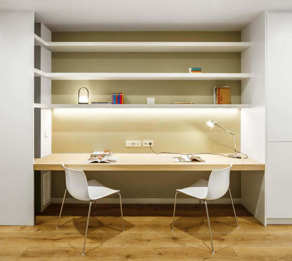 Ejemplo de despacho contemporáneo con paredes beige, suelo de madera en tonos medios, escritorio empotrado y suelo marrón