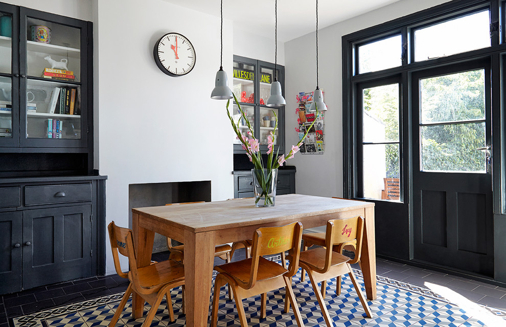Example of a mid-sized danish kitchen/dining room combo design in London with white walls, a standard fireplace and a concrete fireplace