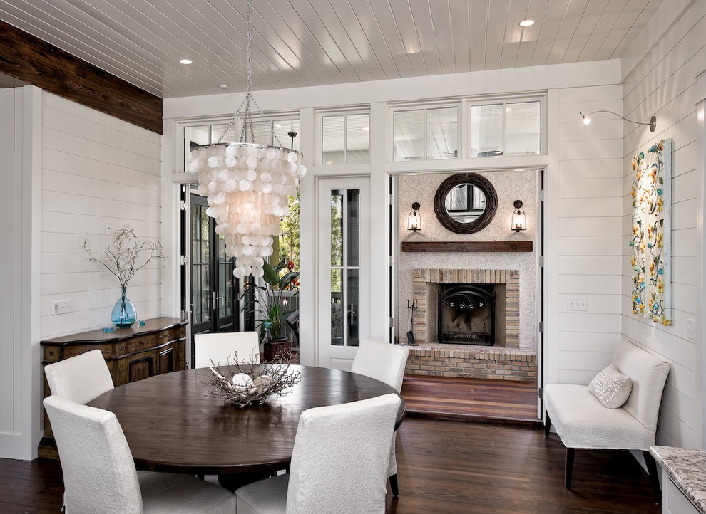Dining room - traditional dark wood floor dining room idea in Miami with white walls and a brick fireplace