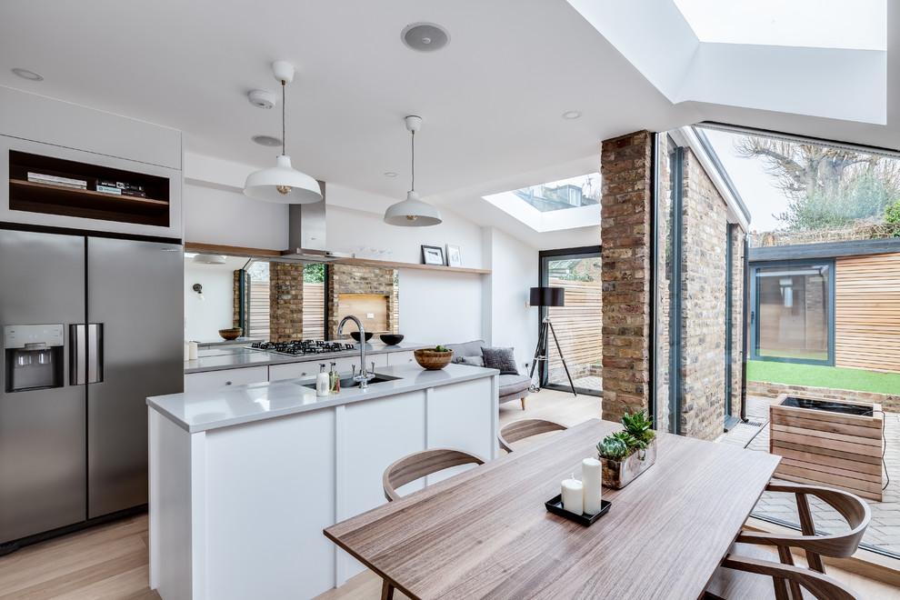 ロンドンの北欧スタイルのおしゃれなダイニングキッチン (白い壁、淡色無垢フローリング) の写真
