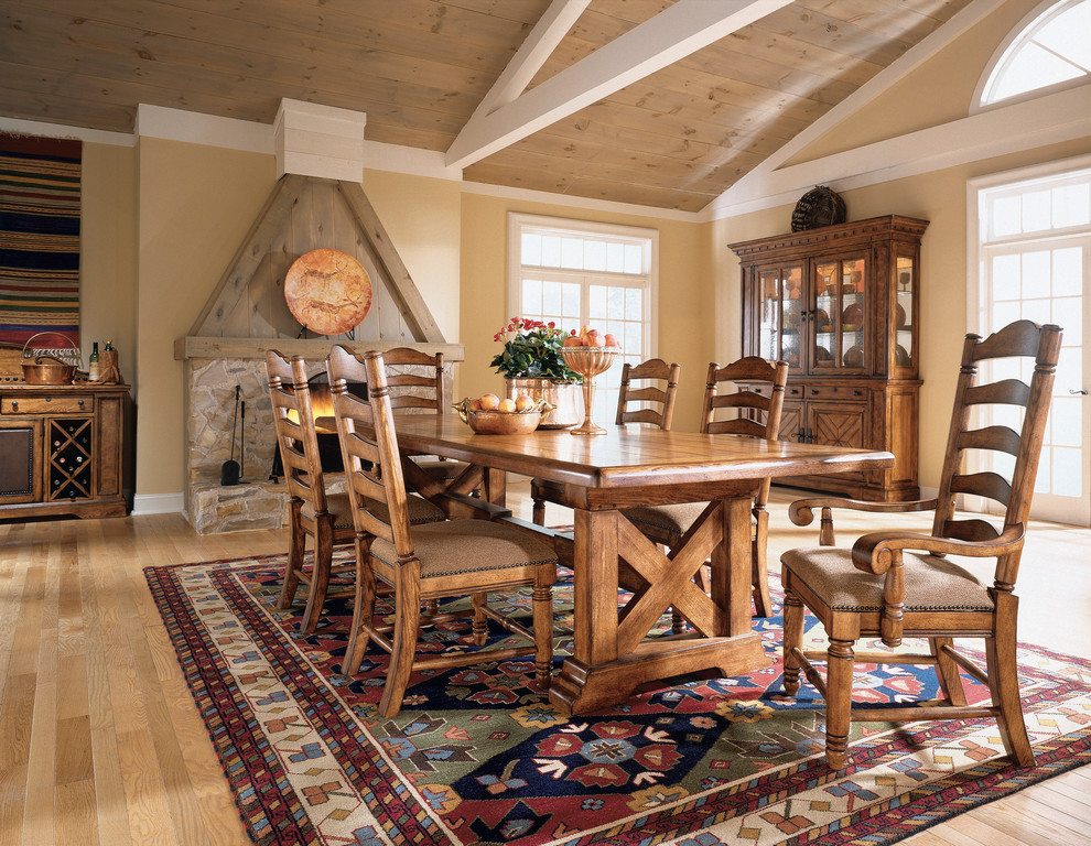 Enclosed dining room - large southwestern light wood floor and beige floor enclosed dining room idea in San Francisco with beige walls, a standard fireplace and a stone fireplace