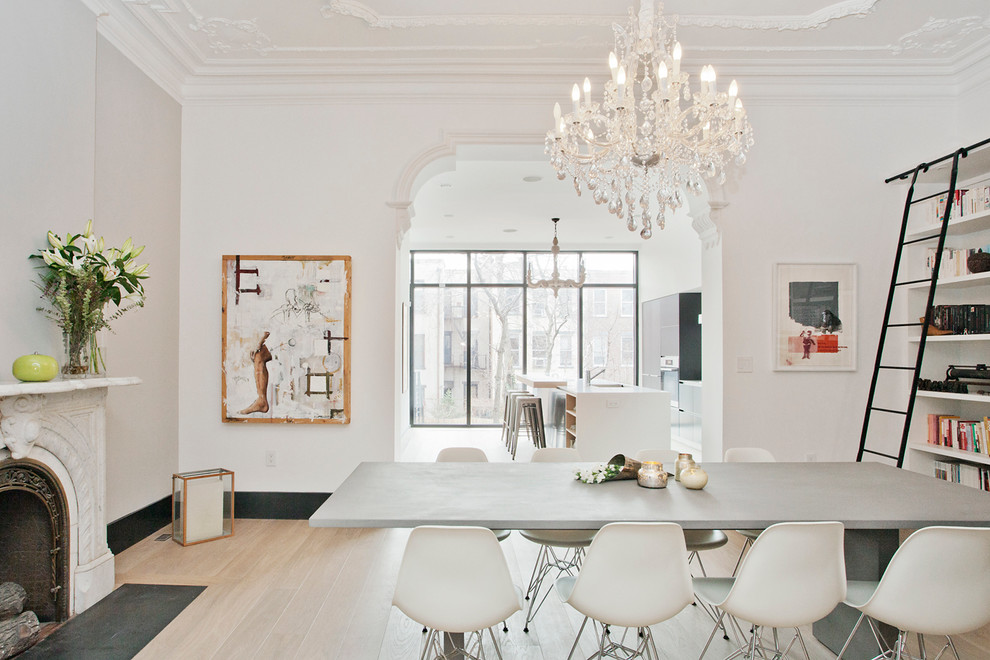 Large danish light wood floor enclosed dining room photo in New York with white walls, a standard fireplace and a stone fireplace