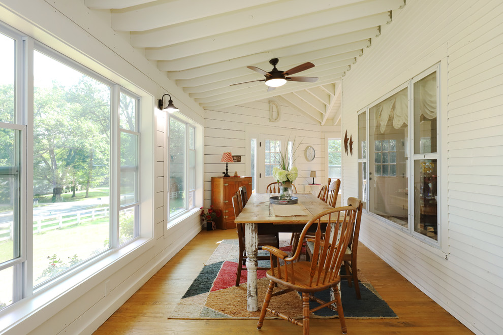Inspiration for a huge farmhouse medium tone wood floor enclosed dining room remodel in Grand Rapids with white walls