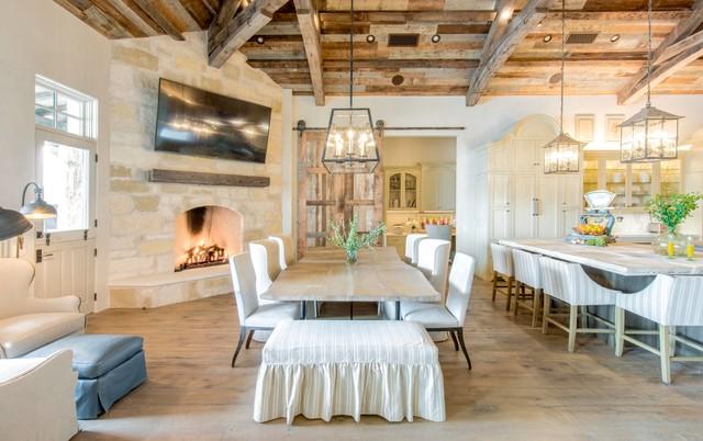 Ispirazione per un'ampia sala da pranzo aperta verso la cucina country con pareti bianche, parquet chiaro, camino ad angolo e cornice del camino in pietra