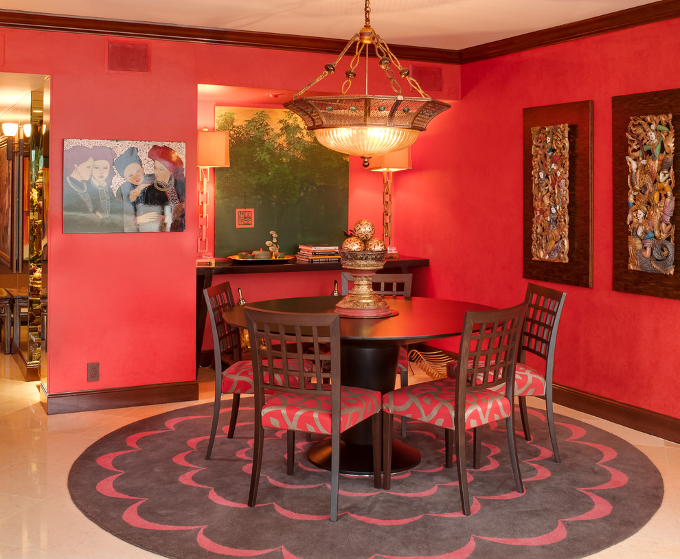 Example of an asian dining room design in Miami with red walls