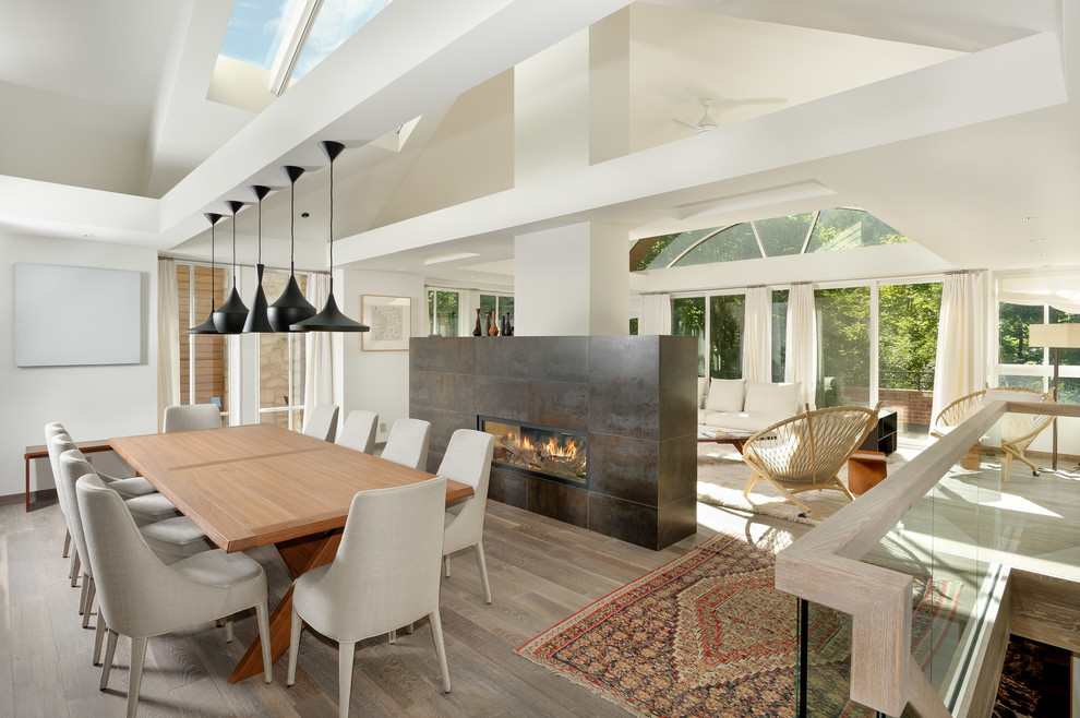 Great room - mid-sized contemporary medium tone wood floor great room idea in Denver with white walls, a two-sided fireplace and a tile fireplace