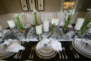 an elegant tablescape with white candles and sprigs of fresh flowers