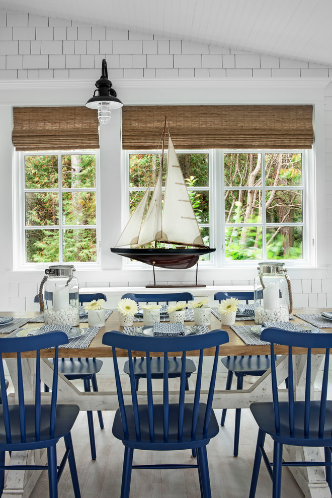 Inspiration for a coastal light wood floor dining room remodel in Other with white walls