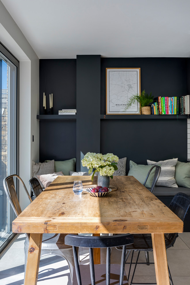 Example of a trendy ceramic tile and gray floor dining room design in London with black walls