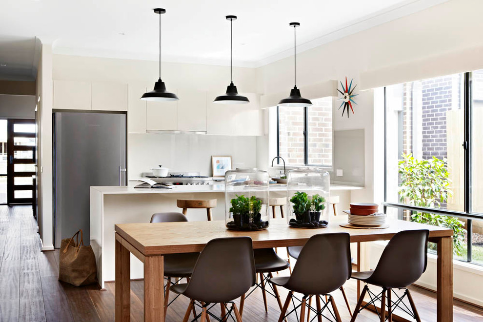 Trendy medium tone wood floor kitchen/dining room combo photo in Melbourne with beige walls and no fireplace
