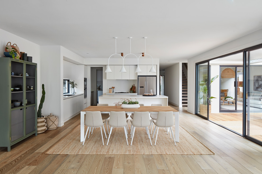 Trendy light wood floor and brown floor great room photo in Melbourne with white walls