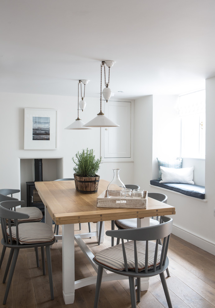 Inspiration for a coastal light wood floor dining room remodel in London with white walls and a wood stove
