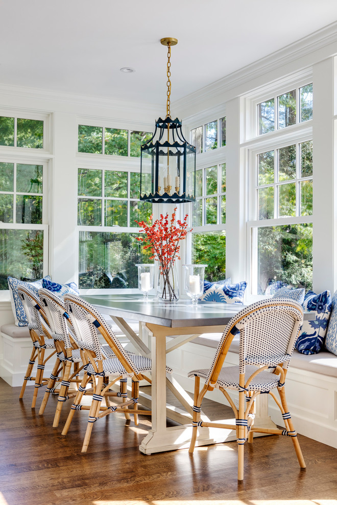 Beach style medium tone wood floor and brown floor dining room photo in Boston with white walls