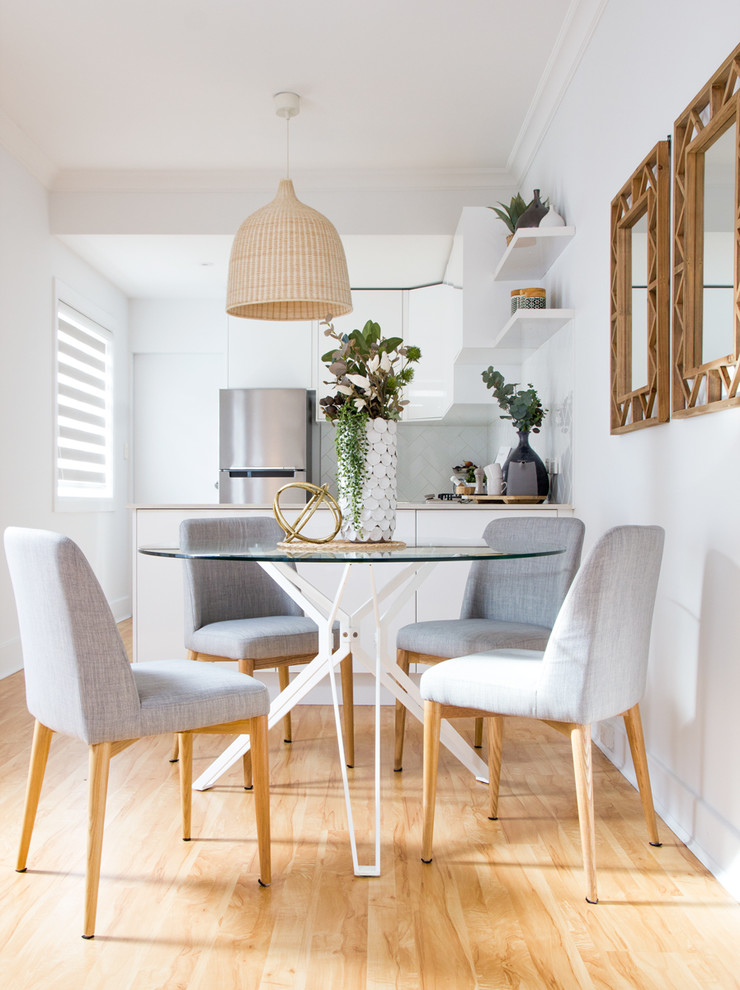 Example of a mid-sized danish light wood floor kitchen/dining room combo design in Sydney with white walls and no fireplace