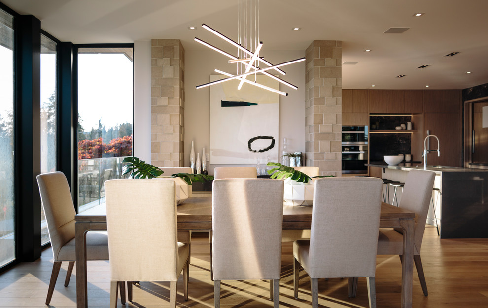 Example of a large trendy medium tone wood floor dining room design in Vancouver