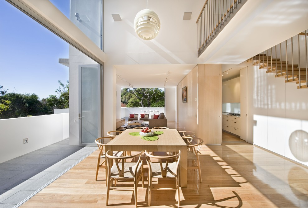 Example of a large trendy light wood floor great room design in Sydney with white walls