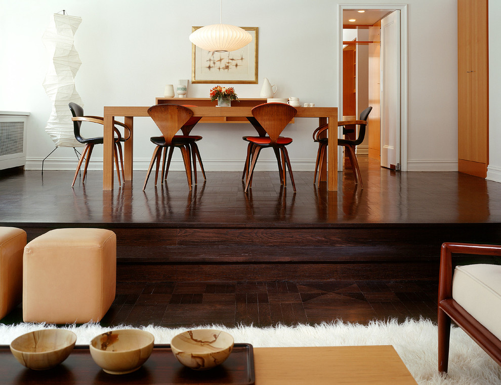 Example of a trendy dark wood floor and brown floor dining room design in New York with white walls