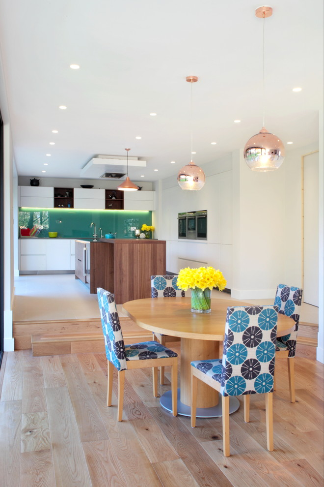 Inspiration for a contemporary light wood floor kitchen/dining room combo remodel in Buckinghamshire with white walls