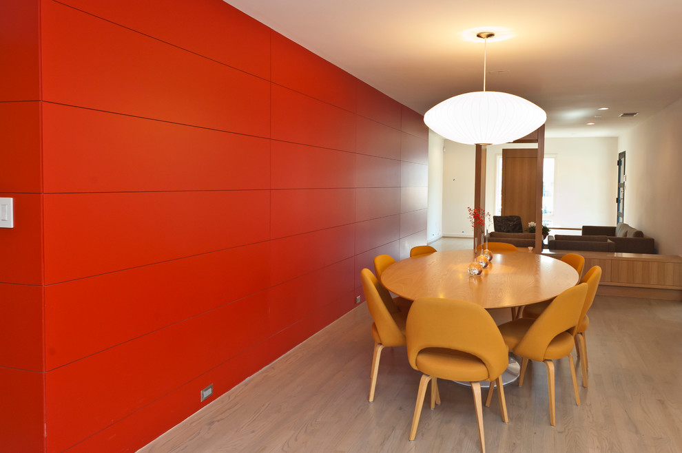Example of a trendy medium tone wood floor dining room design in Dallas with red walls