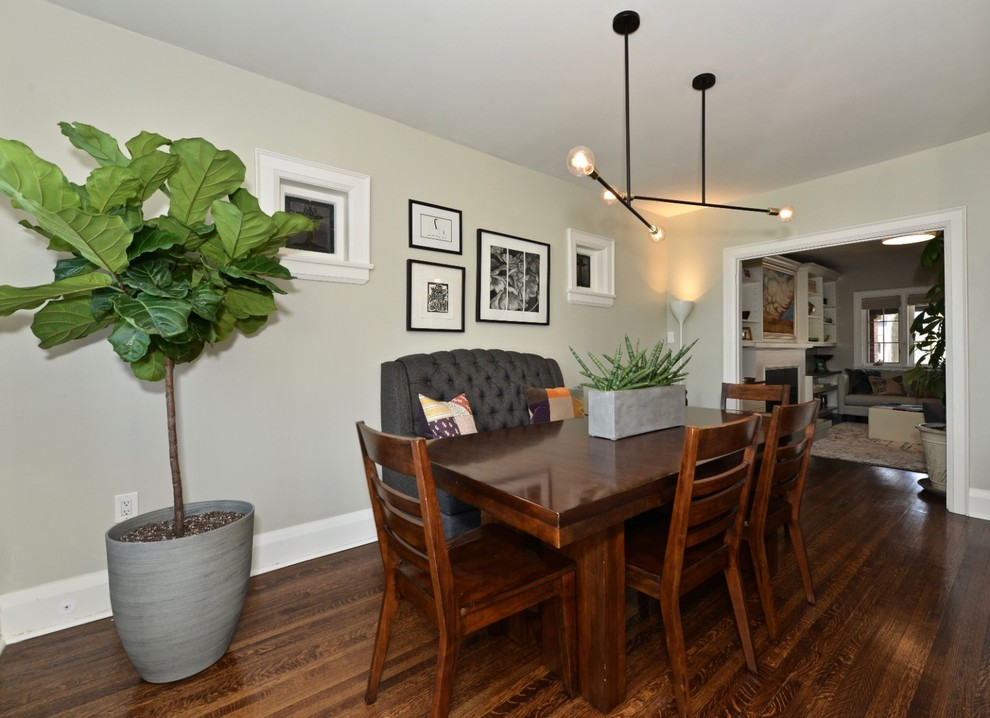 Inspiration for a mid-sized transitional dark wood floor and brown floor kitchen/dining room combo remodel in Toronto with gray walls, a standard fireplace and a tile fireplace