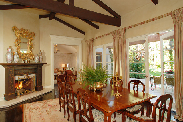 Example of a classic dark wood floor dining room design in Los Angeles with a standard fireplace