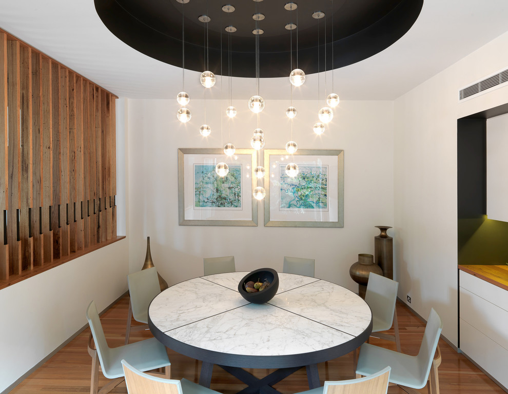 Dining room - contemporary medium tone wood floor dining room idea in Melbourne with white walls