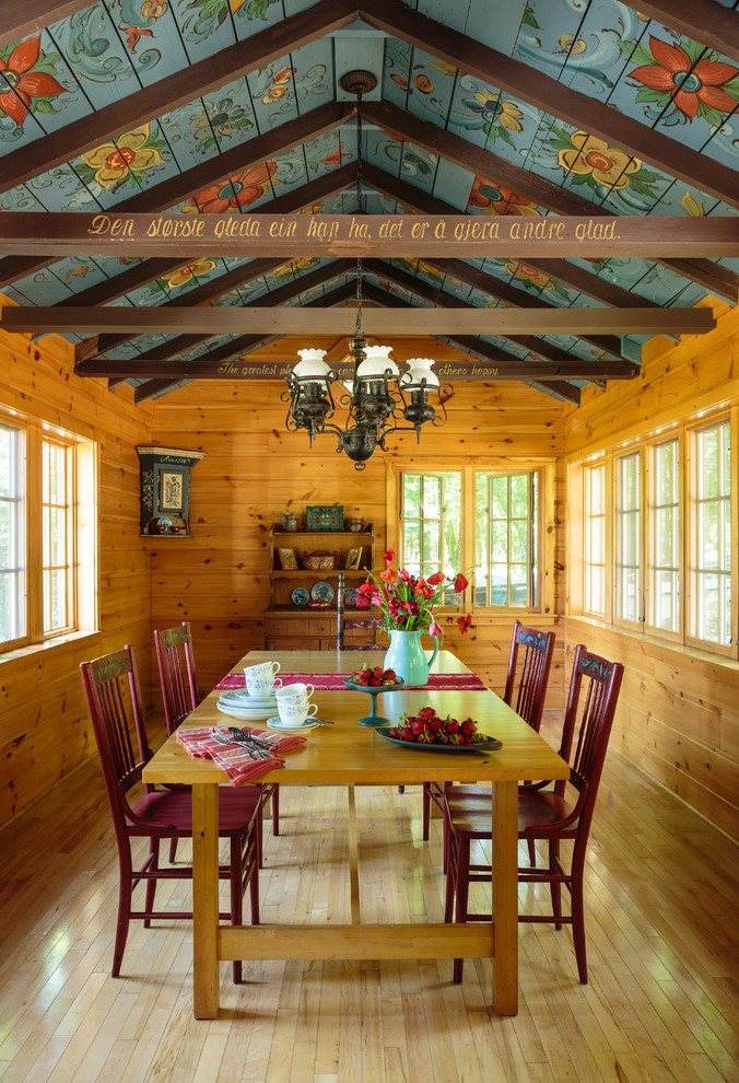 Example of a large country light wood floor and brown floor enclosed dining room design in Milwaukee with brown walls and no fireplace