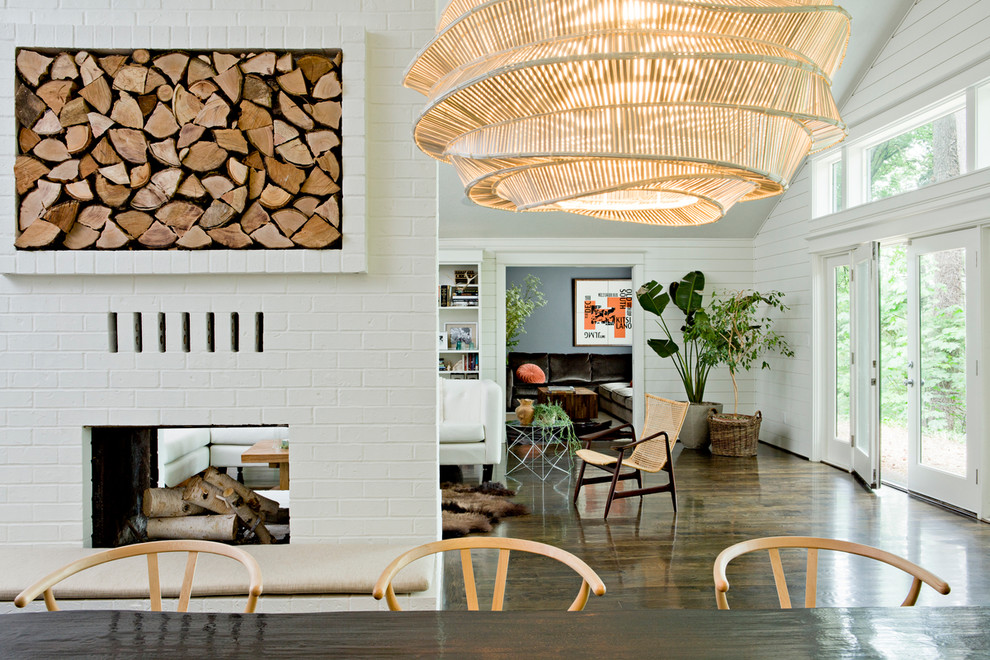 Trendy dark wood floor dining room photo in Portland with a two-sided fireplace and a brick fireplace