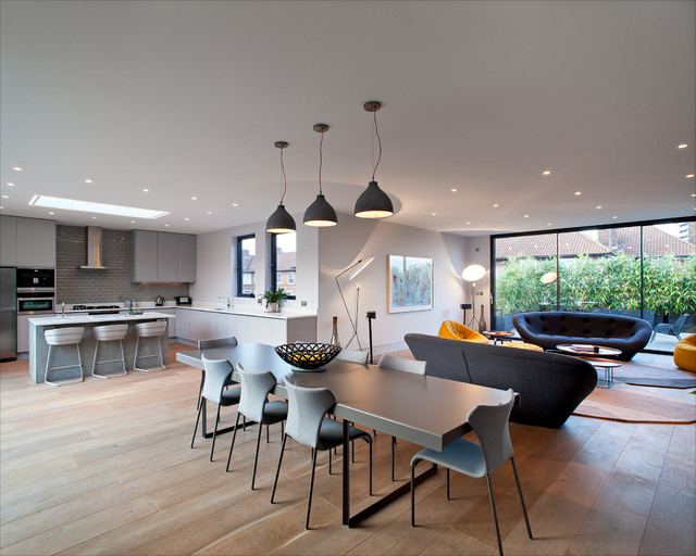Inspiration for a medium sized contemporary open plan dining room in London with white walls and light hardwood flooring.