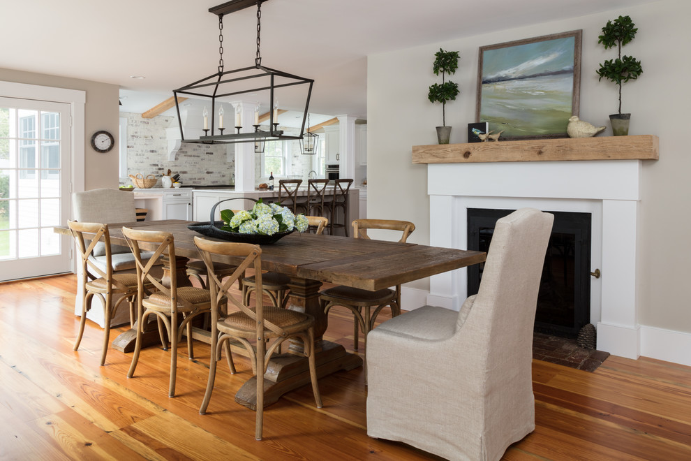 Inspiration for a mid-sized country medium tone wood floor and brown floor kitchen/dining room combo remodel in Boston with beige walls, a standard fireplace and a plaster fireplace
