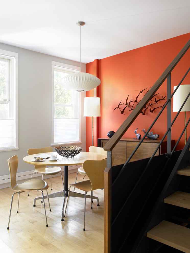 Inspiration for a mid-century modern light wood floor dining room remodel in New York with orange walls