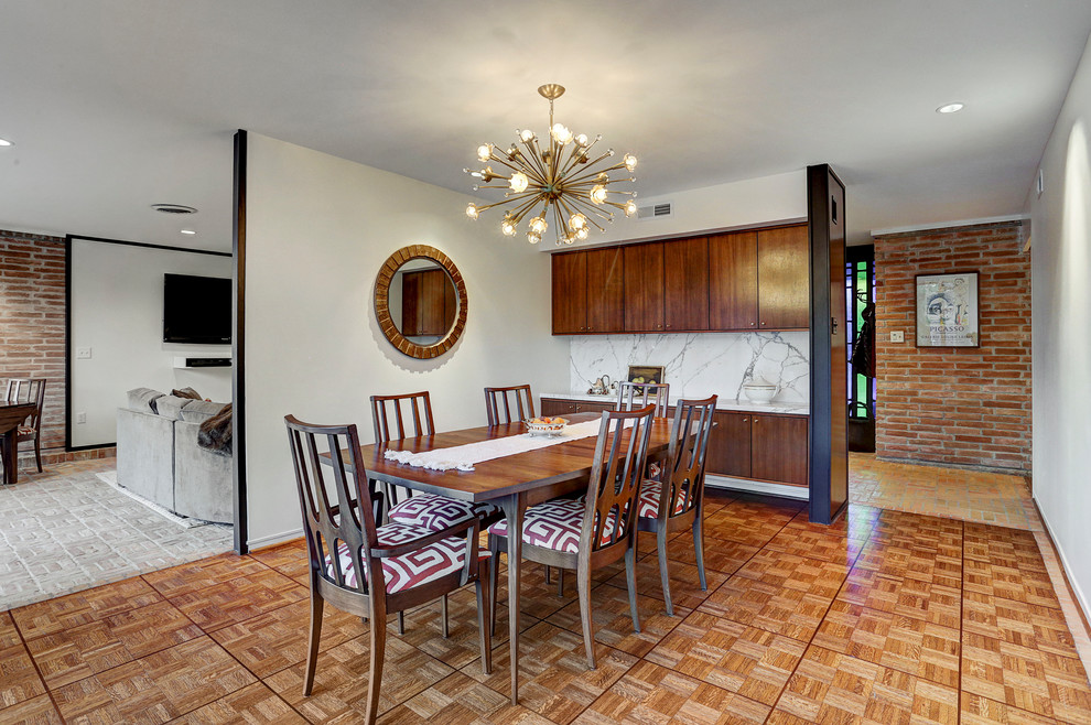Inspiration for a mid-sized 1960s medium tone wood floor and brown floor enclosed dining room remodel in Houston with white walls and no fireplace