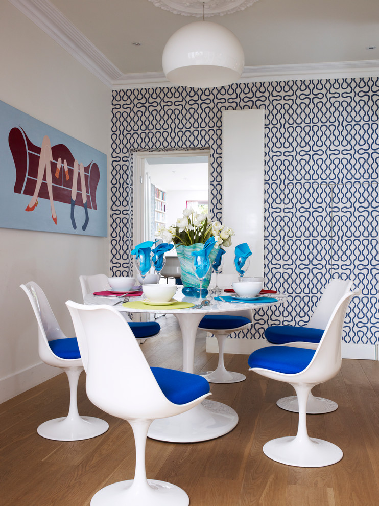 Inspiration for a small contemporary medium tone wood floor enclosed dining room remodel in London with multicolored walls
