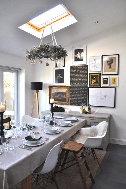 This is an example of a bohemian dining room in London with white walls.