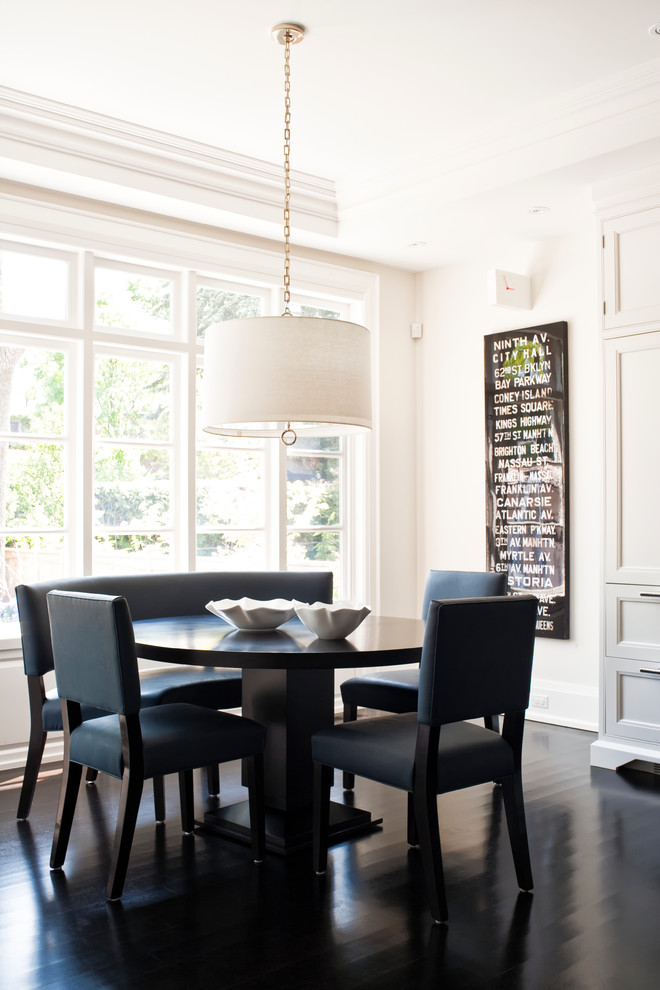 Example of a transitional painted wood floor and black floor dining room design in Toronto with white walls