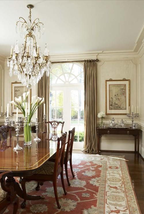 классическая гостиная с невысоким потолком бежевая хрустальная люстра ковер картины