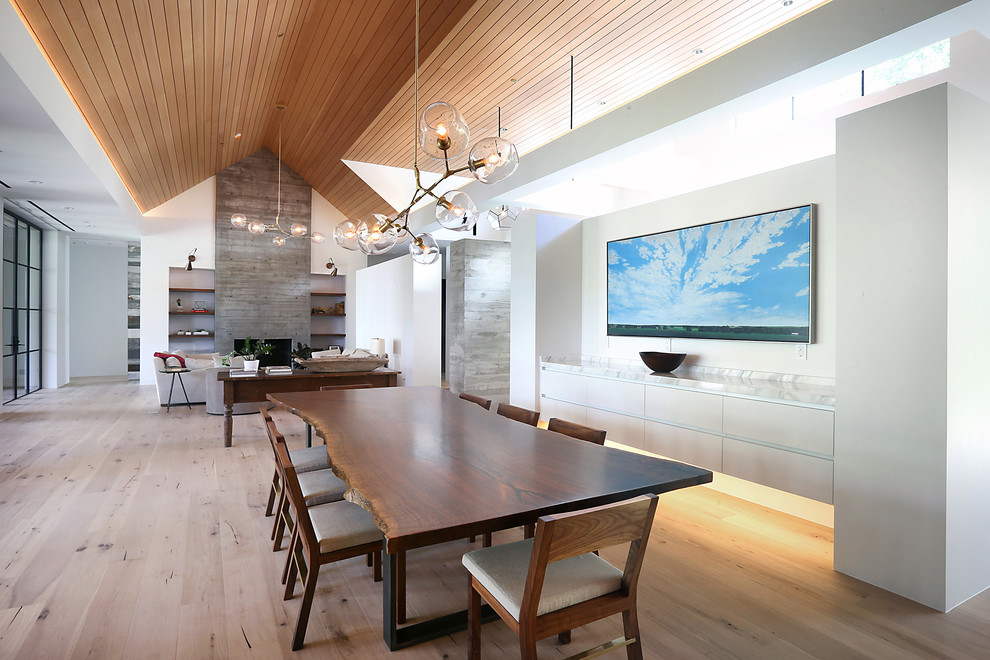 Inspiration for a medium sized contemporary open plan dining room in Denver with white walls, medium hardwood flooring, brown floors, a standard fireplace and a wooden fireplace surround.