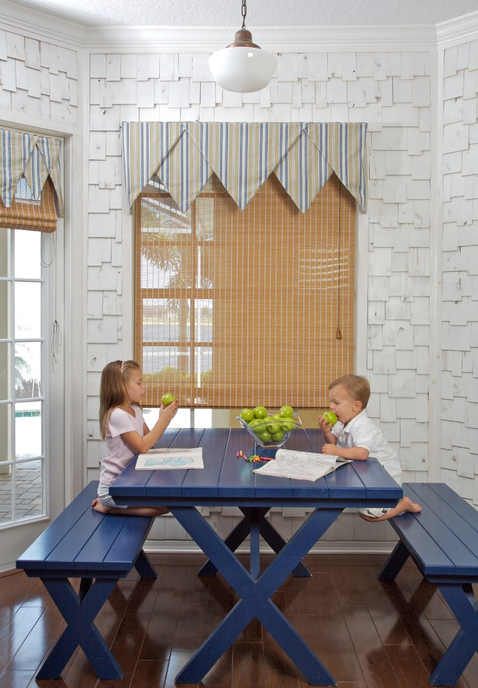 Example of a beach style dark wood floor dining room design in Tampa with white walls