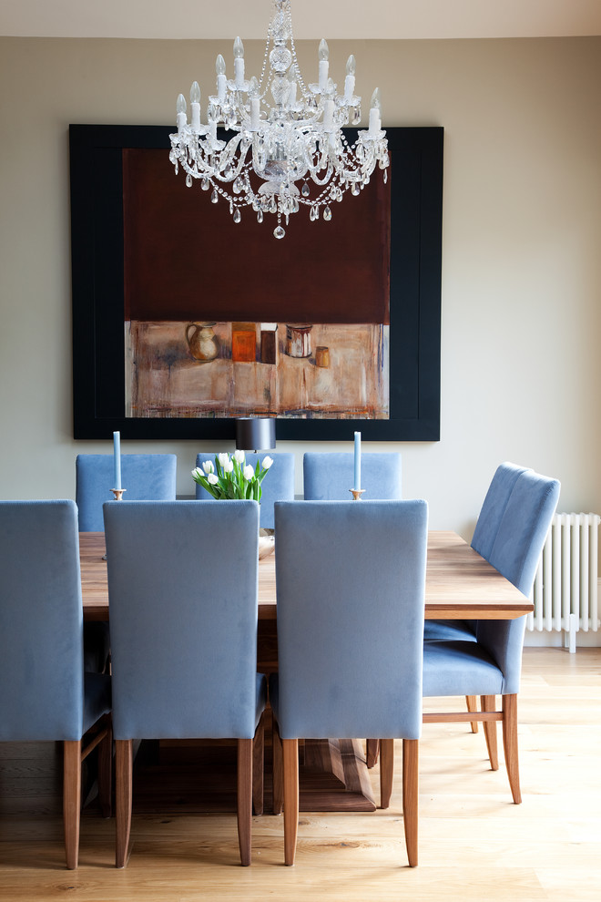 Example of a classic medium tone wood floor dining room design in London with gray walls