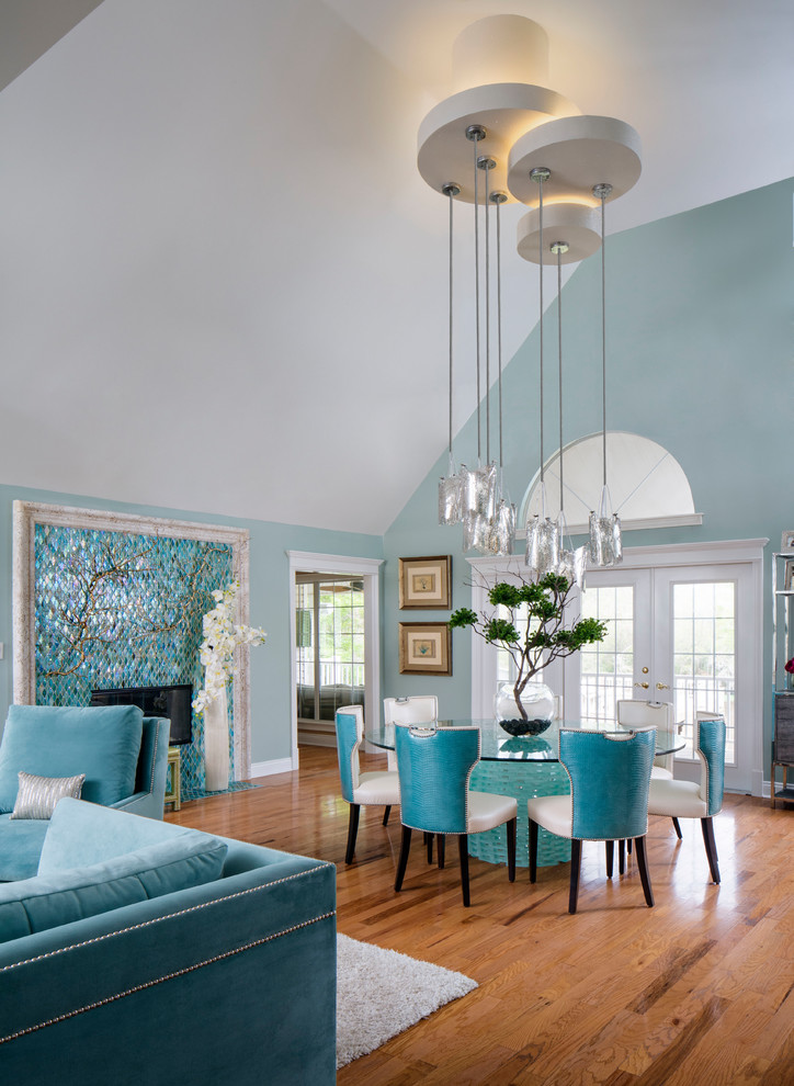 Example of a transitional medium tone wood floor and brown floor dining room design in New Orleans with blue walls, a standard fireplace and a tile fireplace