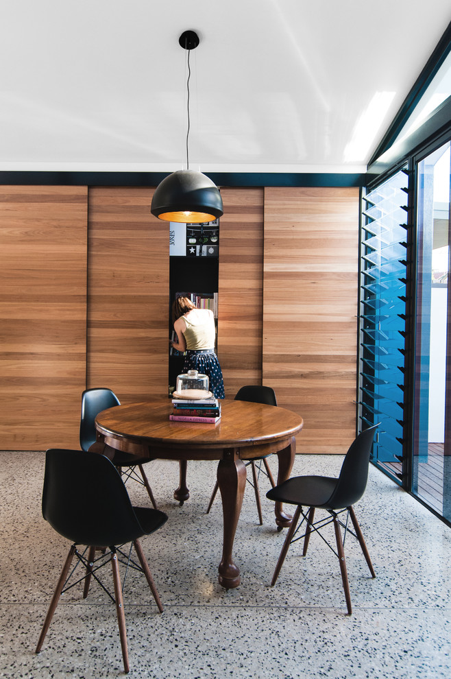 This is an example of a small contemporary kitchen/dining combo in Melbourne with concrete floors.