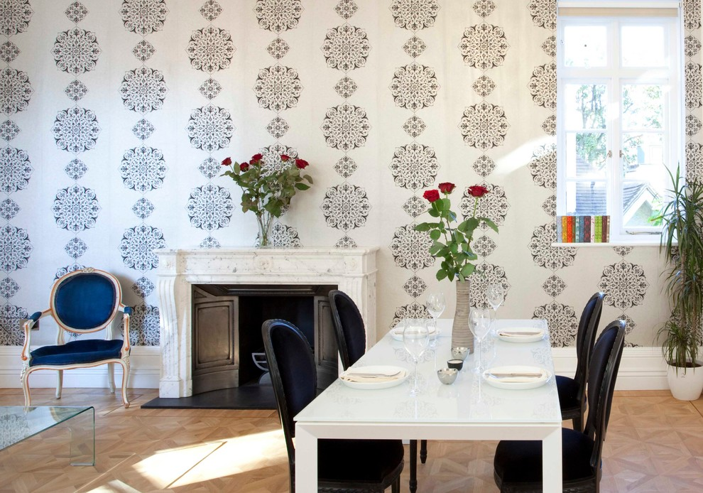 Dining room - contemporary medium tone wood floor dining room idea in London with a standard fireplace