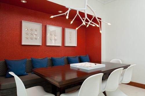 comedor con una pared de fondo roja con cuadros blancos