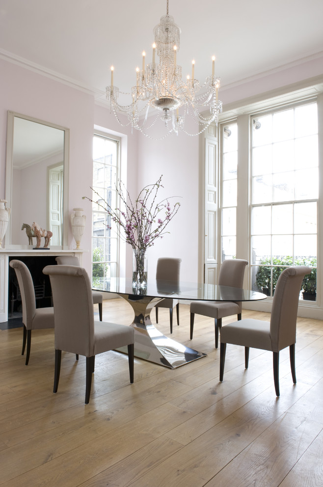 Large trendy light wood floor dining room photo in London with pink walls, a standard fireplace and a plaster fireplace